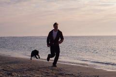 Mężczyzna bieg z psem Zdjęcia Royalty Free