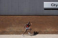 Mężczyzna bieg Za ściana z cegieł Z 'miastem' Pisać Na Nim Obraz Stock