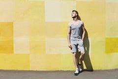 Mężczyzna biegacz ma przerwę, opiera przy kolor żółty ścianą obrazy stock