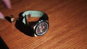 Mężczyzna bierze jasnozielonego gatunku zegarek od drewnianej powierzchni stół _ Ręki akcesorium zbiory