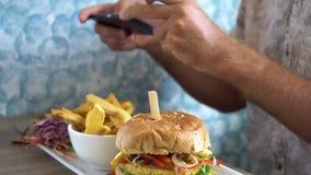 Mężczyzna bierze mobilnych obrazki hamburger z francuskimi dłoniakami Ogólnospołeczny Medialny styl życia zbiory