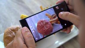 Mężczyzna bierze mobilnych obrazki hamburger z francuskimi dłoniakami Ogólnospołeczny Medialny styl życia zbiory wideo