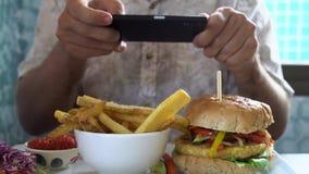 Mężczyzna bierze mobilnych obrazki hamburger z francuskimi dłoniakami Ogólnospołeczny Medialny styl życia zdjęcie wideo
