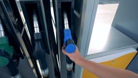 Mężczyzna bierze nozzle dla paliwa przy benzynową stacją zbiory