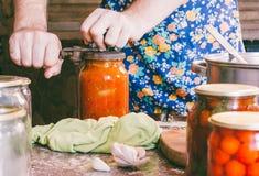 Mężczyzna bierze ona w konserwować starą nieociosaną kuchnię Fotografia Royalty Free