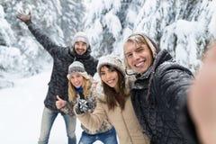 Mężczyzna Bierze Selfie fotografii przyjaciołom uśmiech Śnieżni Lasowi młodzi ludzie grupa Plenerowa Zdjęcia Royalty Free