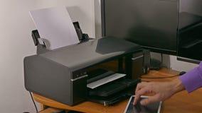 Mężczyzna biznesmen w biurze drukuje dokumenty na drukarce pisać na maszynie na pastylce zbiory wideo