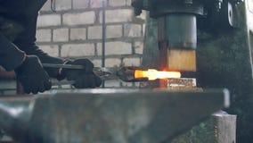 Mężczyzna blacksmith fałszuje metal przy machinalnym młotem - mały biznes zbiory