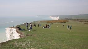 Mężczyzna blisko do krawędzi i patrzeć nad pobliskim Beachy Kierowniczy Wschodni Sussex zbiory wideo
