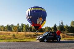 Mężczyzna blisko samochodowego dopatrywania jako dwa gorące powietrze balonu ląduje na polu przy festiwalem aeronautyka w Peresla obraz stock