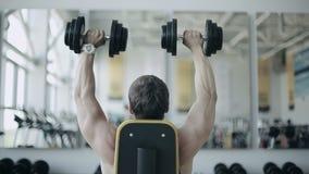 Mężczyzna bodybuilder wykonuje ćwiczenie z dumbbells w gym Materiał filmowy tylny ciało zbiory wideo