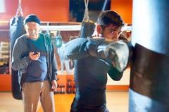 Mężczyzna boksu torba z trenerem na treningu fotografia stock
