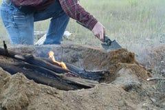 Mężczyzna budów ogienia jama Wokoło Otwartego obozu ogienia Zdjęcie Royalty Free