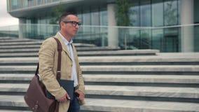 Mężczyzna chodzi blisko nowożytnego budynku zbiory wideo