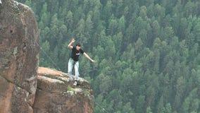 Mężczyzna chodzi na arkanie rozciągającej przy wysokością między dwa szczytami w Syberyjskim rezerwacie przyrody Stolby zdjęcie wideo