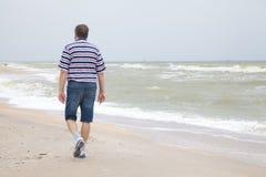 Mężczyzna chodzi na dennej plaży Fotografia Royalty Free
