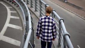 Mężczyzna chodzi nad mostem w mieście zbiory