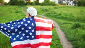 M??czyzna chodzi oddalonego, tylni widok na ramionach jego USA flaga, Patriotyczny dzie? dzie? pami?? nie?ywy amerykanin zdjęcie wideo
