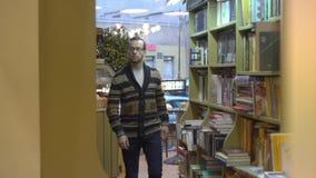 Mężczyzna chodzi wśród półek na książki To jest biblioteka lub bookstore zbiory wideo