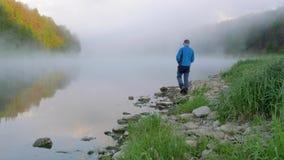 Mężczyzna chodzi wzdłuż brzeg rzekiego z kamieniami za błękitne wody zbiory
