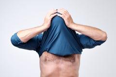 Mężczyzna chuje jego twarz z podkoszulkiem Istota ludzka chował głowę z koszulką obraz stock