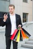 Mężczyzna chwyt zdojest podczas gdy czek dyskontowy z smartphone online Facet niesie wiązek torba na zakupy Zyskowne transakcje r obraz stock