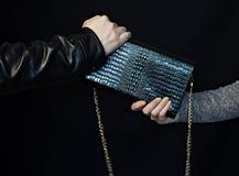 Mężczyzna chwyta torebkę od ręk kobieta, czarny tło, kradzież torby zdjęcia stock