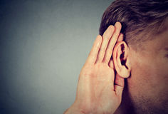 Mężczyzna chwyty wręczają blisko ucho i słuchają ostrożnie Zdjęcia Stock