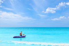 Mężczyzna ciągnięcia kajak w morzu na niebieskie niebo wakacje wakacje summ obrazy royalty free