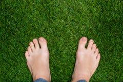 Mężczyzna cieki stoi na trawy zakończeniu up Zdjęcie Royalty Free