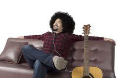 Mężczyzna cieszyć się muzyczny i relaksować na kanapie Zdjęcia Royalty Free