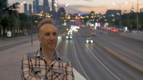 Mężczyzna cieszy się miasto widok przeciw ulicie i budynkom przy zmierzchem zbiory