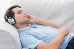 Mężczyzna cieszy się muzycznego lying on the beach na leżance Fotografia Stock
