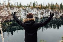 Mężczyzna cieszy się pięknego jeziornego widok od hilltopl i dobrą pogodę w Karelia Wokoło skał zdjęcie stock