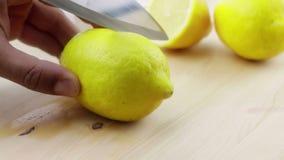 Mężczyzna, ciie wewnątrz plasterek, zdrowie i odżywianie żółta cytryna z nożem na drewnianej ciapanie desce w kuchni, zdjęcie wideo