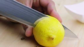 Mężczyzna, ciie wewnątrz plasterek, zdrowie i odżywianie żółta cytryna z nożem na drewnianej ciapanie desce w kuchni, zbiory