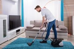 Mężczyzna cleaning dywan z próżniowym cleaner obrazy stock