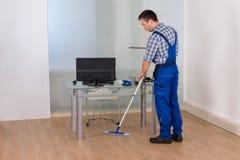 Mężczyzna cleaning podłoga w biurze Fotografia Stock