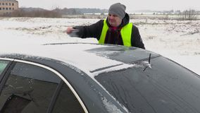 Mężczyzna cleaning samochód od śniegu