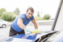 Mężczyzna cleaning samochód z gąbką zdjęcie royalty free