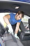 Mężczyzna cleaning samochód z hoover fotografia stock