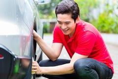 Mężczyzna cleaning samochodowi obręcze z gąbką Fotografia Stock