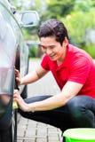Mężczyzna cleaning samochodowi obręcze z gąbką Zdjęcia Royalty Free
