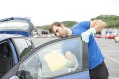 Mężczyzna cleaning samochodowy szkło z gąbką obraz stock