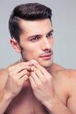 Mężczyzna cleaning twarzy skóra z uderzać bawełnianych ochraniaczów fotografia stock