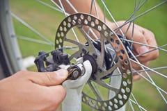 Mężczyzna cyklista sprawdza hamulcowego koło bicykl obraz stock