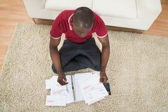 Mężczyzna cyrklowania faktury Używać kalkulatora Zdjęcie Royalty Free