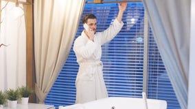 Mężczyzna czekać na początek postępowania z telefonem w ręce, stoi bezczynnie panoramicznego okno z widokiem zbiory