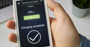 Mężczyzna czeki ładują poziom jego elektryczny samochód Bateria ładuje Samochodowy pilot do tv używać smartphone zastosowanie zbiory wideo
