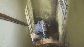 Mężczyzna czyści ściany silny brud z muśnięciem i łachmanem Pracownik myje korytarz ściany ręcznie Foremka i zbiory